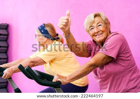 Portrait of happy Senior fitness woman doing thumbs up at spinning session in gym. - stock photo