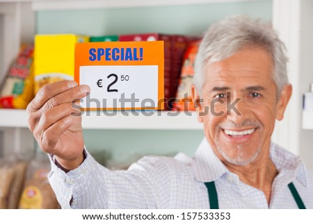 Portrait of happy senior male owner showing discount sign in grocery store - stock photo