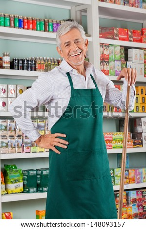 Portrait of happy senior male owner standing against shelves in grocery store - stock photo