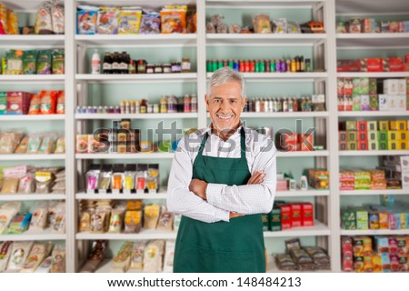 Portrait of happy senior male owner standing arms crossed against shelves in supermarket - stock photo