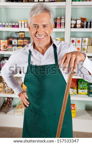 Portrait of happy senior male owner with stick standing in grocery store - stock photo