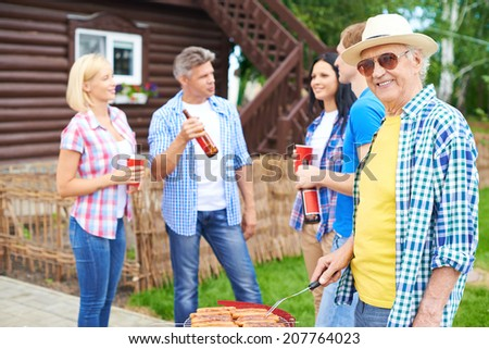 Portrait of happy senior man frying sausages and looking at in the countryside at weekend with group of young friends talking on background - stock photo