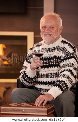 Portrait of happy senior man having wine at home in front of fireplace, hand on chess set, smiling at camera.? - stock photo