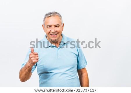 Portrait of happy senior man showing thumb up.Happy senior man with thumb up - stock photo