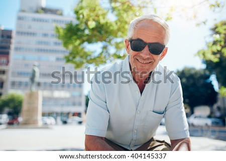 Portrait of happy senior man sitting outside in the city. Mature man with sunglasses outdoors on a summer day. - stock photo