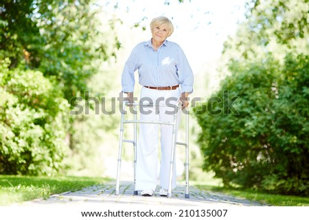 Portrait of happy senior patient walking in the park in summer - stock photo