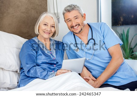 Portrait of happy senior woman and male caretaker with tablet PC in bedroom at nursing home - stock photo