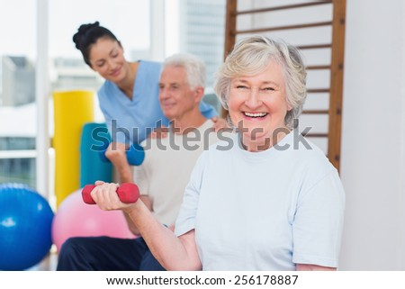 Portrait of happy senior woman lifting dumbbells while sitting with man and instructor in gym - stock photo