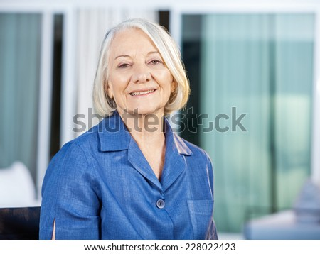 Portrait of happy senior woman sitting at nursing home yard - stock photo