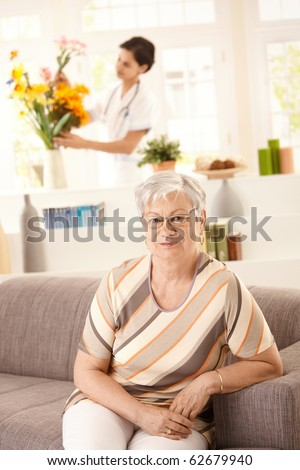 Portrait of happy senior woman sitting on sofa at home, nurse arranging flowers in background.? - stock photo