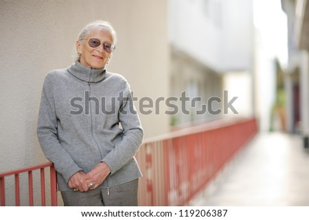 Portrait of happy senior woman standing outside building - stock photo