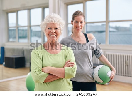 Portrait of happy senior woman standing with her arms crossed and her personal trainer in background gym. Caucasian elderly woman at health club with gym instructor. - stock photo
