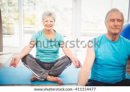 Portrait of happy senior woman with husband meditating at home - stock photo