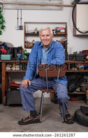 Portrait of happy senior worker sitting in his workshop. - stock photo