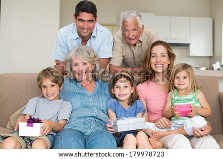 Portrait of happy siblings holding gifts with family in living room - stock photo