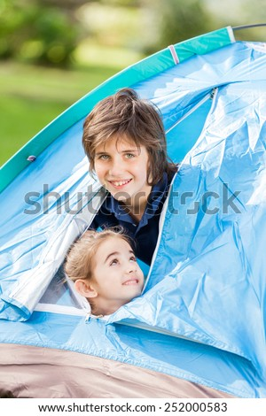 Portrait of happy siblings in tent at park - stock photo