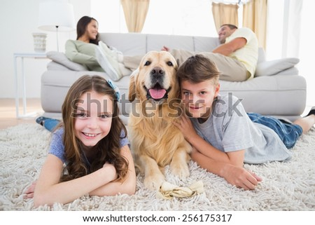 Portrait of happy siblings lying with dog while parents resting on sofa at home - stock photo