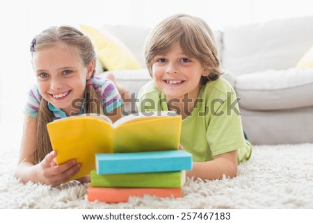 Portrait of happy siblings reding book while lying on rug in living room - stock photo
