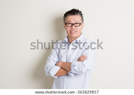 Portrait of happy single mature 50s Asian man in casual business arms crossed smiling and standing over plain background with shadow. - stock photo