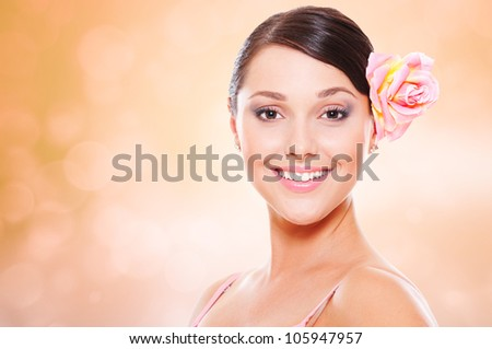 portrait of happy smiley model with rose in hair - stock photo
