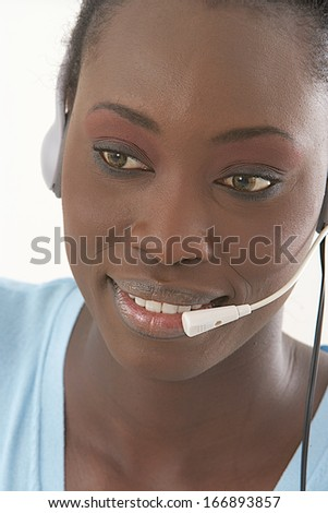 Portrait of happy smiling and beautiful African-American  support phone operator with headset - stock photo