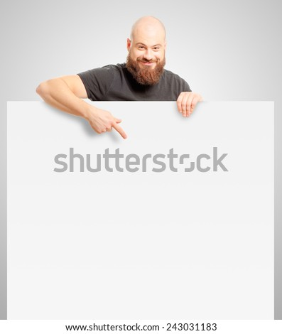 Portrait of happy smiling bald man with a long beard holding banner and pointing on white background - stock photo