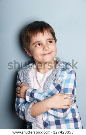 Portrait of happy smiling beautiful boy looking up, studio shot - stock photo