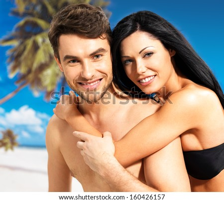Portrait of  happy smiling beautiful couple in love  at tropical beach - stock photo