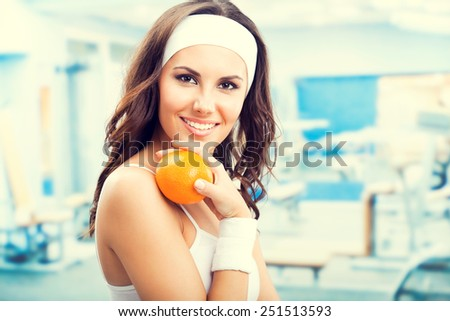 Portrait of happy smiling beautiful woman with orange, at fitness center or gym - stock photo