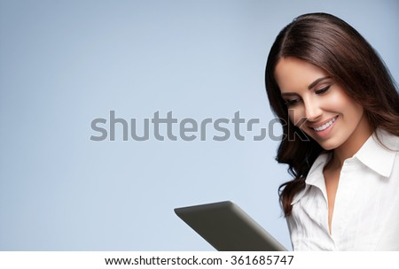 Portrait of happy smiling beautiful young brunette businesswoman using no-name tablet pc, with blank copyspace area for slogan or text message, over grey background - stock photo