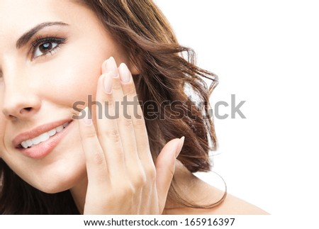 Portrait of happy smiling beautiful young woman touching skin or applying cream, isolated over white background - stock photo