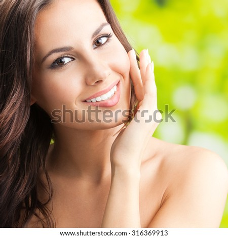 Portrait of happy smiling beautiful young woman touching skin or applying cream, outdoors, square composition - stock photo