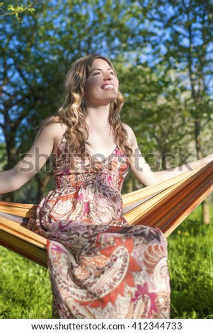 Portrait of Happy Smiling Blond Female Resting in Hummock in Spring Forest Outdoors.Vertical Image - stock photo