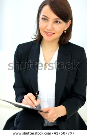 Portrait of happy smiling business woman with black folder - stock photo