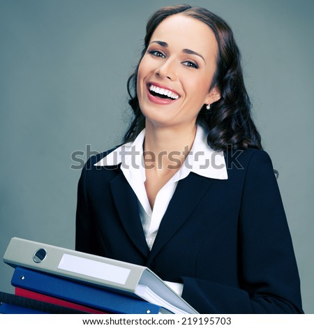 Portrait of happy smiling business woman with folders, over gray background - stock photo