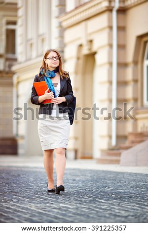 Portrait of happy smiling business woman with red folder in city - stock photo