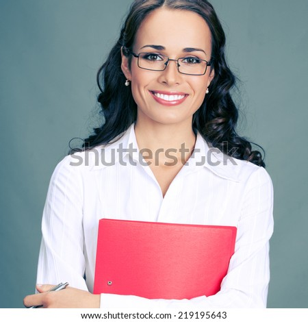 Portrait of happy smiling business woman with red folder, over gray background - stock photo