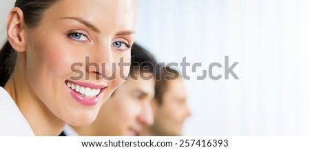 Portrait of happy smiling businesswoman and colleagues at office, with copyspace area for slogan or text - stock photo
