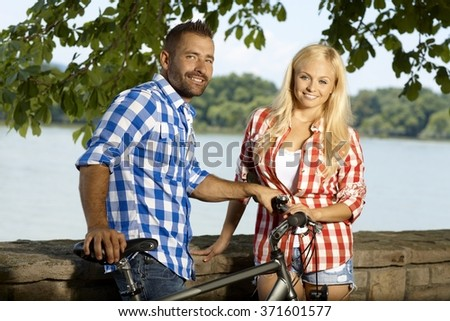 Portrait of happy smiling casual couple with bicycle outdoor. Handsome man and attractive woman, looking at camera. - stock photo