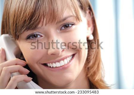 Portrait of happy smiling cheerful beautiful young business woman or support phone worker, at office - stock photo