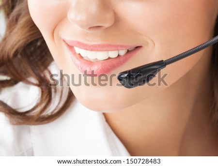 Portrait of happy smiling cheerful beautiful young support phone operator in headset - stock photo