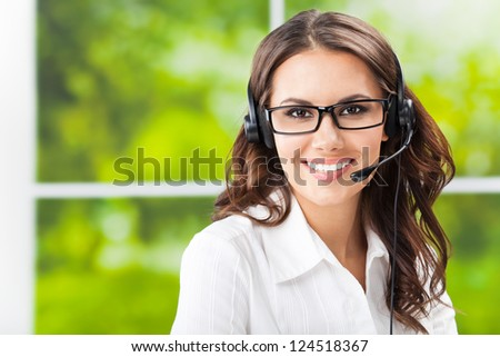 Portrait of happy smiling cheerful beautiful young support phone operator in headset, at office, with copyspace - stock photo