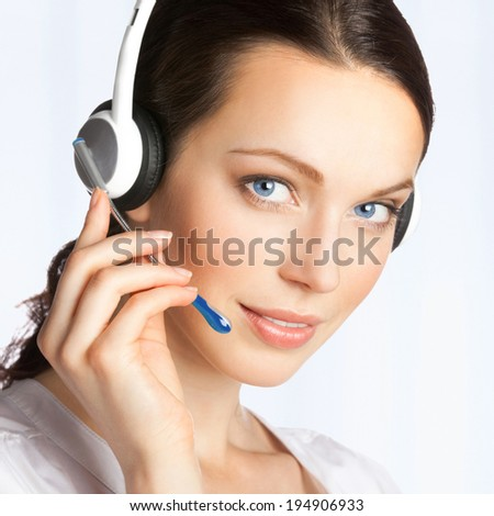 Portrait of happy smiling cheerful beautiful young support phone operator in headset, at office - stock photo