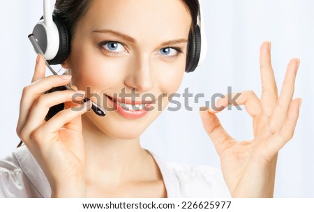 Portrait of happy smiling cheerful beautiful young support phone operator in headset showing okay gesture, at office - stock photo