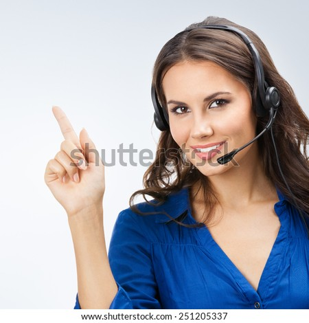 Portrait of happy smiling cheerful beautiful young support phone operator showing - stock photo