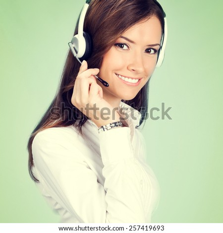 Portrait of happy smiling cheerful customer support phone operator in headset, on green background - stock photo