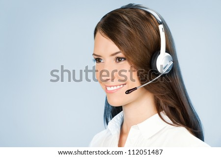Portrait of happy smiling cheerful customer support phone operator in headset, over blue background - stock photo