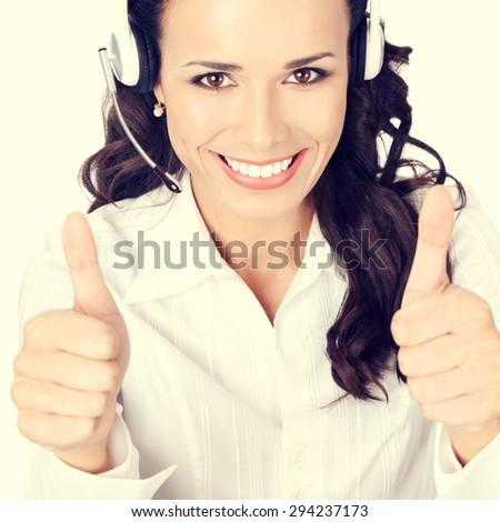 Portrait of happy smiling cheerful customer support phone operator or businesswoman in headset showing thumbs up hand sign gesture - stock photo