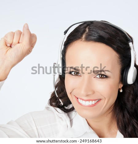 Portrait of happy smiling cheerful gesturing customer support phone operator in headset, against grey background - stock photo