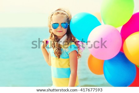 Portrait of happy smiling child on summer beach with colorful balloons over sea - stock photo